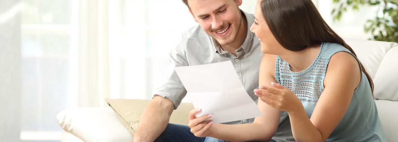 gelukkig paar, thuis op bank, goed nieuws, hypotheek, lezen mail, lezen brief
