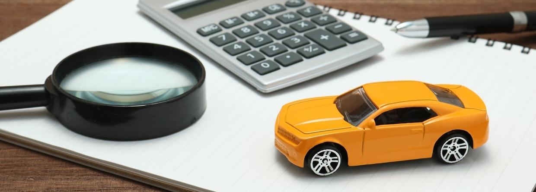 Notitieblok waarop een speelgoedauto, vergrootglas, rekenmachine en pen ligt