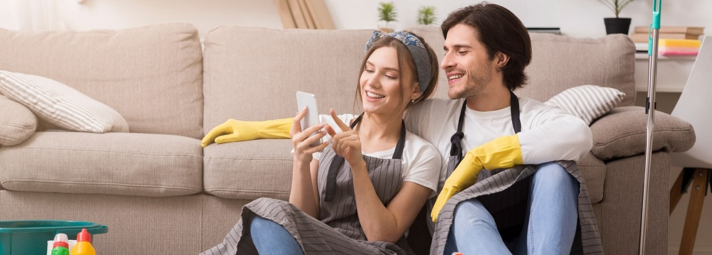 gelukkig stel kijkt tijdens het schoonmaken op de telefoon