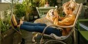 een vrouw geniet met haar hond op het terras