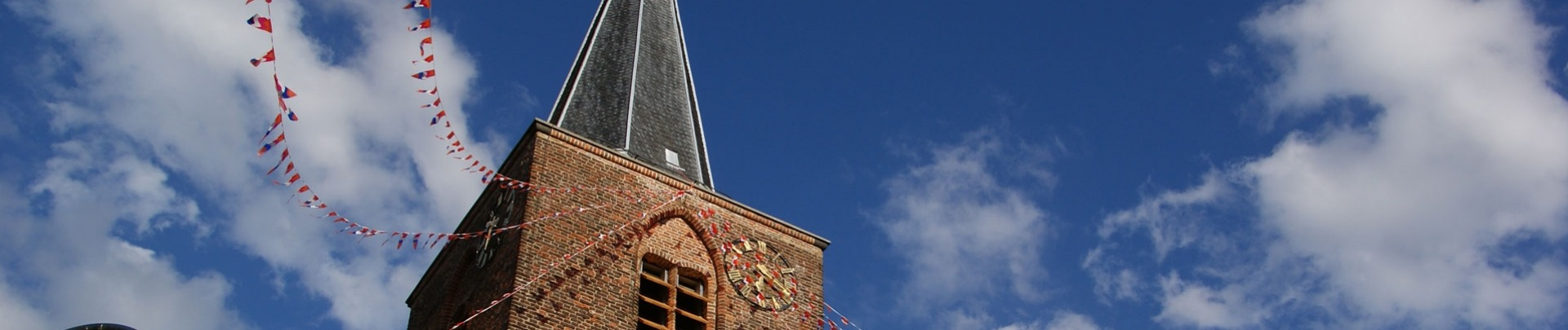 Kerktoren versierd met vlaggetjes